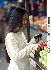 Young asian woman holding vegetables at market