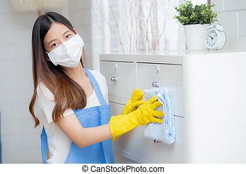 Young asian woman in face mask and gloves cleaning home in room, housekeeper is wipe with fabric, housemaid and service, worker polish dust in house, housework and domestic, lifestyle concept.