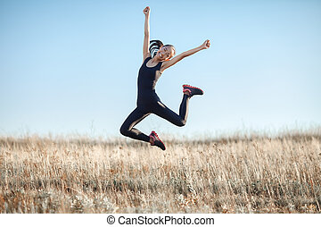 Young Asian woman in sports clothes happy jumping outdoors