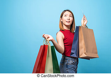 Young Asian woman in summer wear carrying shopping bags on blue background. Concept of shopping, summer sale.