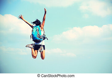 young asian woman jumping against blue sky