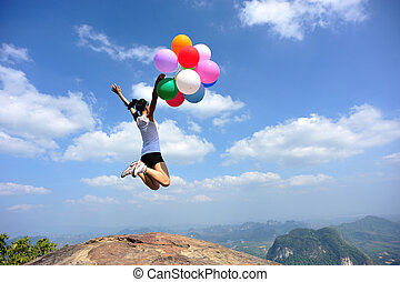 young asian woman jumping on mountain peak rock with colored...