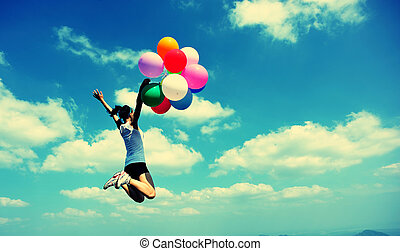 young asian woman jumping to blue sky with colored balloons