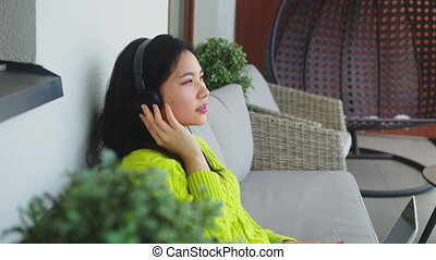 Young asian woman listening to the music from the laptop using headphones. Freelancng or distance learning concept. High quality 4k footage