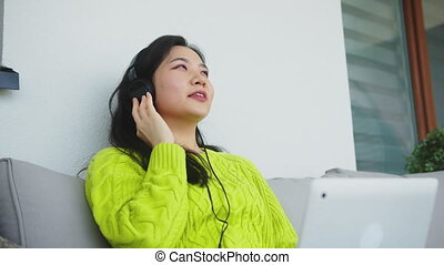 Young asian woman listening to the music from the laptop using headphones. High quality 4k footage