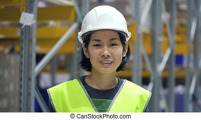 Young asian woman looking at camera with smile during working day at warehouse.