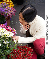 Young asian woman looking at flowers at store