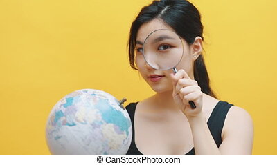 Young asian woman looking at the globe through the magnifier.