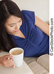 Young asian woman lying on the sofa reading a book holding her coffee in living room at home
