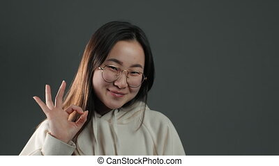 Young asian woman making OK sign over grey background. Winner. Success. Positive korean girl smiles to camera. Body language
