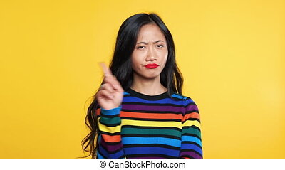 Young asian woman nod her head and make no finger sign. ...