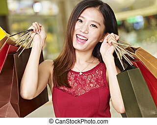 young asian woman on a shopping spree - young asian woman on...