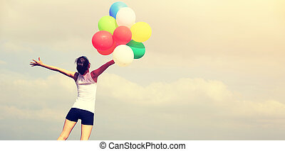 young asian woman on mountain peak rock with colored balloons