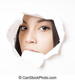 young asian woman peeking through hole torn in paper wall