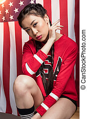 young asian woman posing in front of USA flag, Independence Day of America
