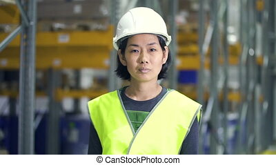 Young asian woman posing with smile, standing in industrial warehouse while working day.
