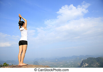 young asian woman practice yoga on mountain peak cliff