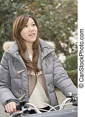 Young Asian woman riding bicycle