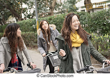 Young Asian woman riding bicycle with friends