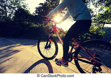 young asian woman riding bike on forest trail