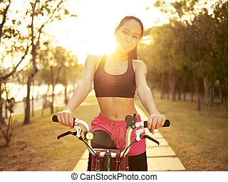 young asian woman riding bike outdoors at sunset