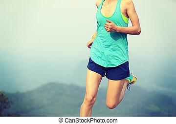 young asian woman runner running on mountain peak