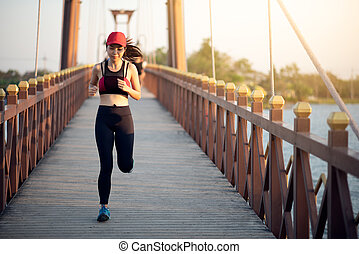 Young Asian woman runner running on the bridge in the morning