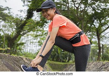 Young asian woman runner tying shoelaces