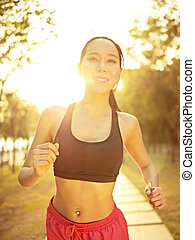 young asian woman running in park