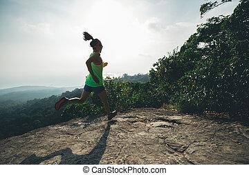 Young asian woman running on mountain peak