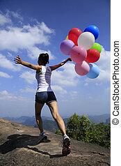 woman running on mountain peak