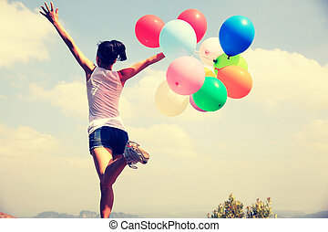 young asian woman running on mountain peak rock with colored balloons