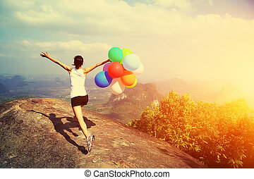 young asian woman running on mountain peak rock with colored...