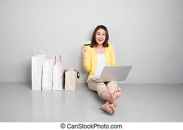Young asian woman shopping online at home sitting besides row of shopping bags