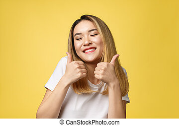 Young Asian woman show thumbs up on yellow background