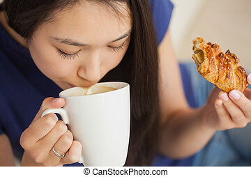 Young asian woman sipping her coffee and holding a pastry