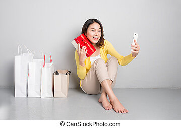 Young asian woman sitting besides row of shopping bags holding red gift box taking sellfie