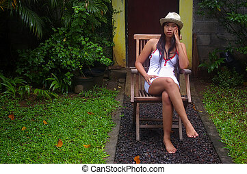 Asian woman sitting in a garden