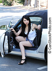 Young asian woman sitting in car short skirt