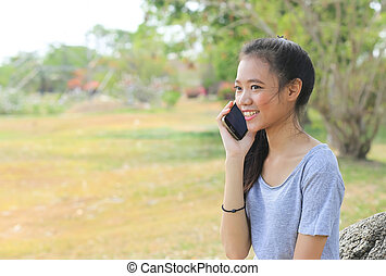 woman sitting on stone using a mobile telephone