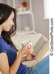 Young asian woman sitting on the sofa reading a book holding her coffee in living room at home