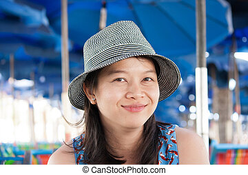 Young asian woman smiling at camera outdoors