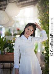 Young Asian woman smiling in garden.