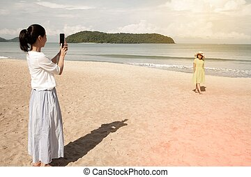 Young asian woman standing on the beautiful nice blue beach with white sand and taking photo with smartphone.
