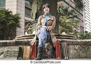 young asian woman taking a break while shopping