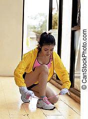 Young asian woman tying her shoelace