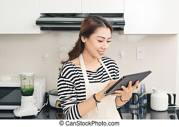 Young asian woman using a tablet computer to cook in her kitchen.