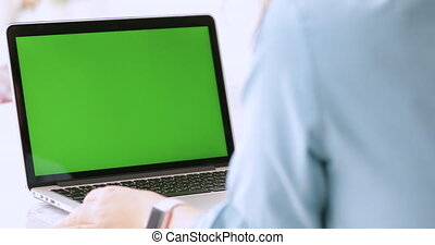 Young asian woman using laptop computer with green screen.