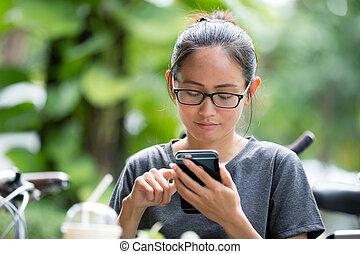 Young Asian woman using smartphone in garden