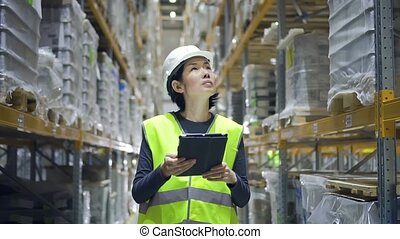 Young asian woman using tablet while walking in warehouse of modern factory.